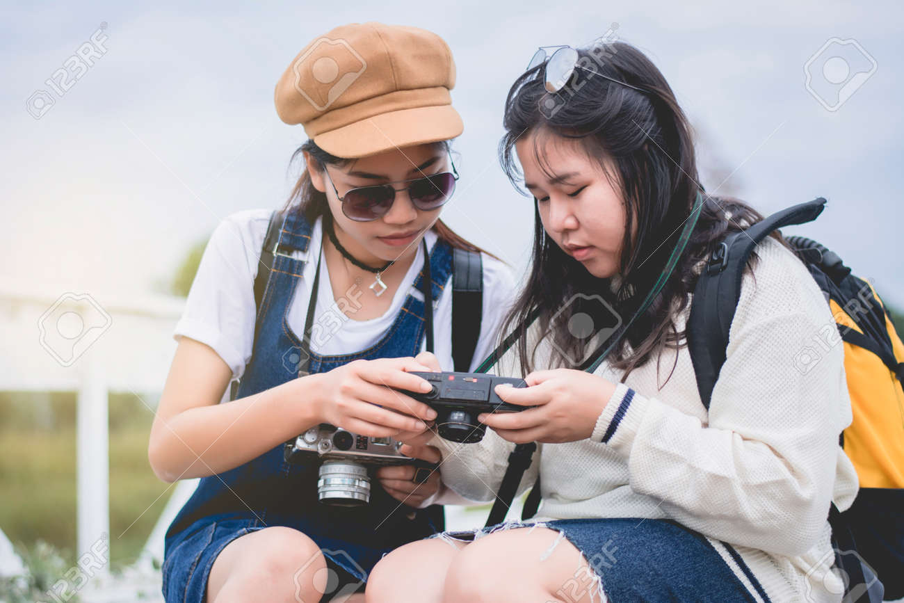 Two trendy cool hipster girls, friends, on the old wooden bridge, and backpacks, holding vintage camera, positive emotions. - 160605636