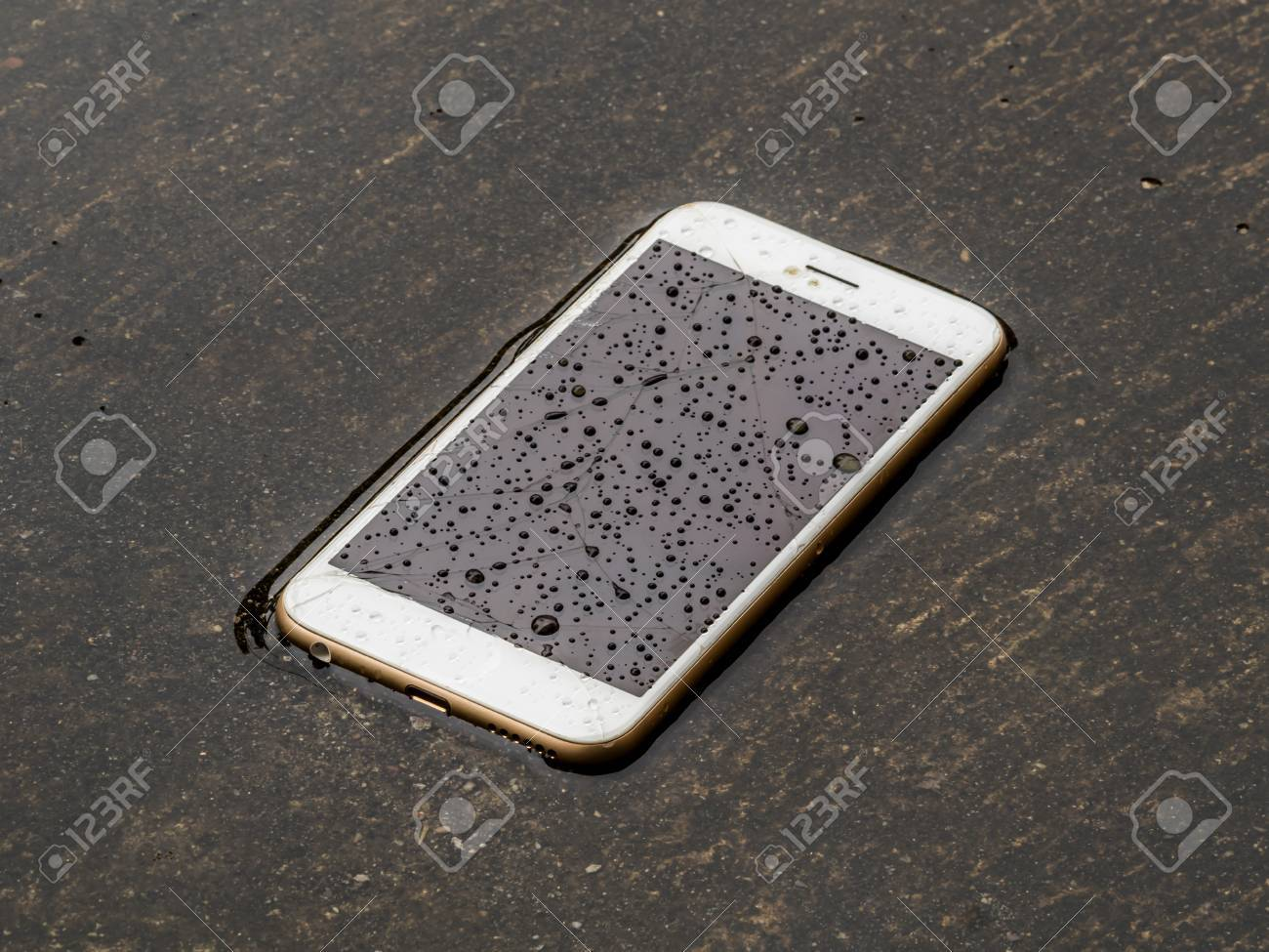 Damage and wet smart phone dropped on flooding floor with water