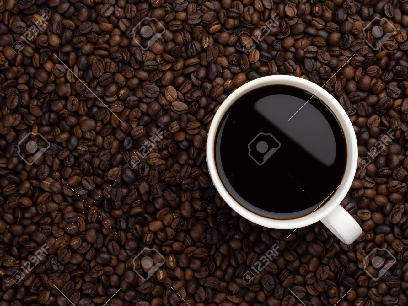 Close-up and top view of hot black coffee in white coffee cup on roasted coffee beans background with area for copy space - 142188237
