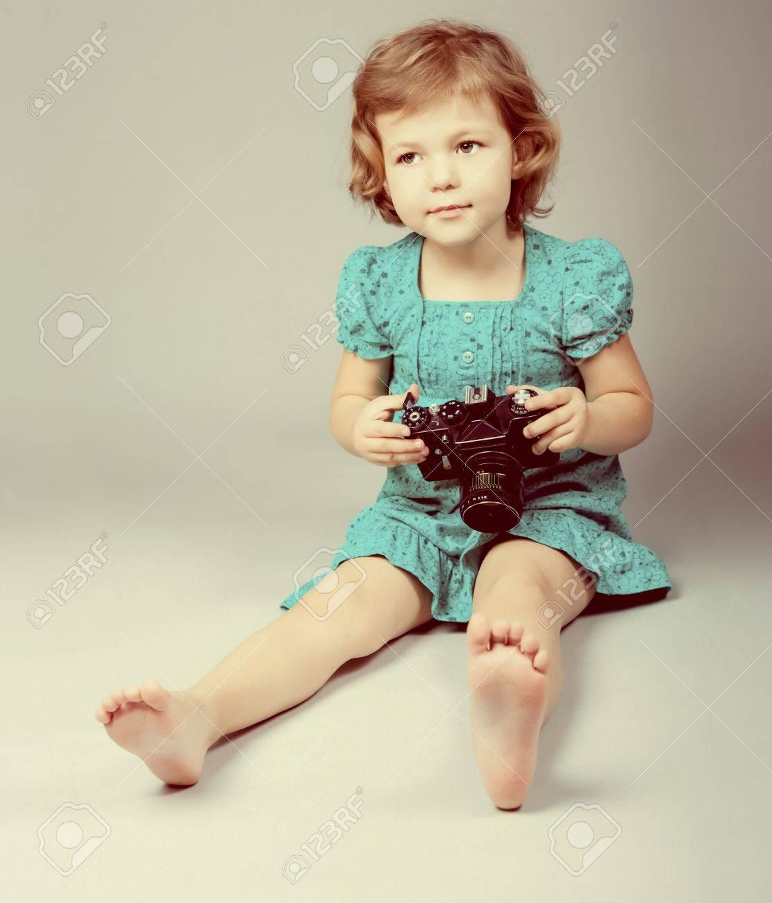 Portrait of baby girl holding photo camera Stock Photo - 13086612