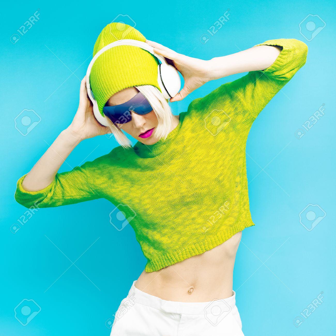 Glamorous Lada DJ in fashionable sportswear listening to Musik on blue background - 36050086