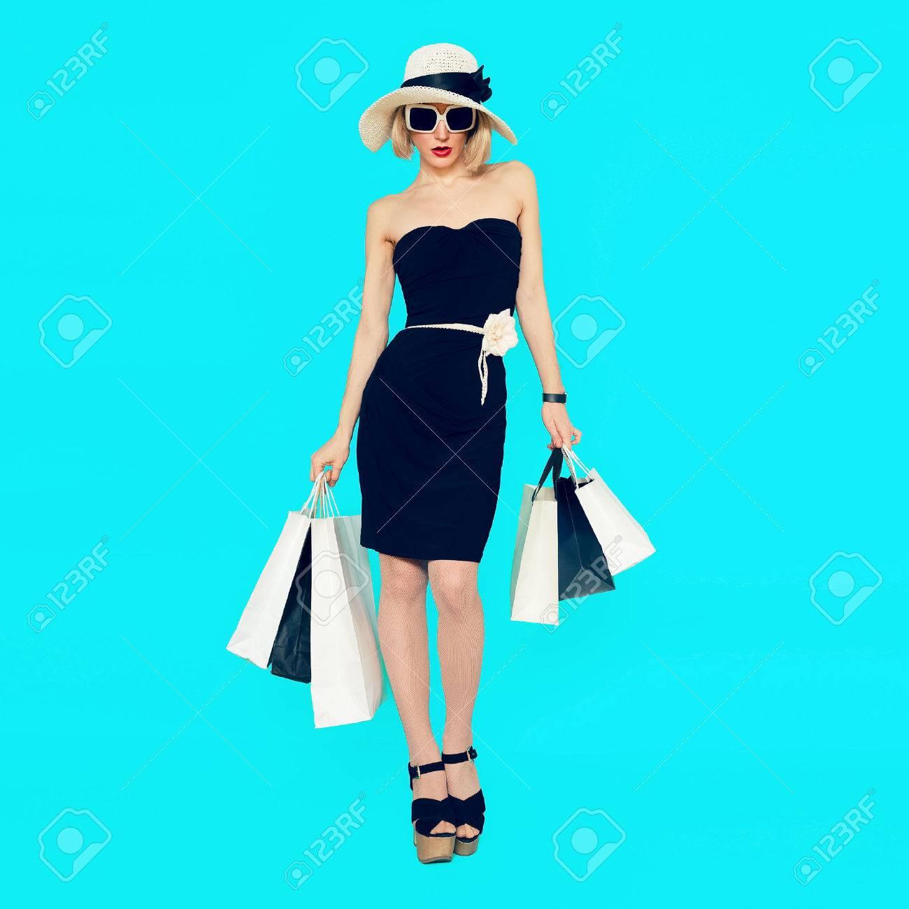 Stylish shopping lady with shopping bags on blue background - 44776668
