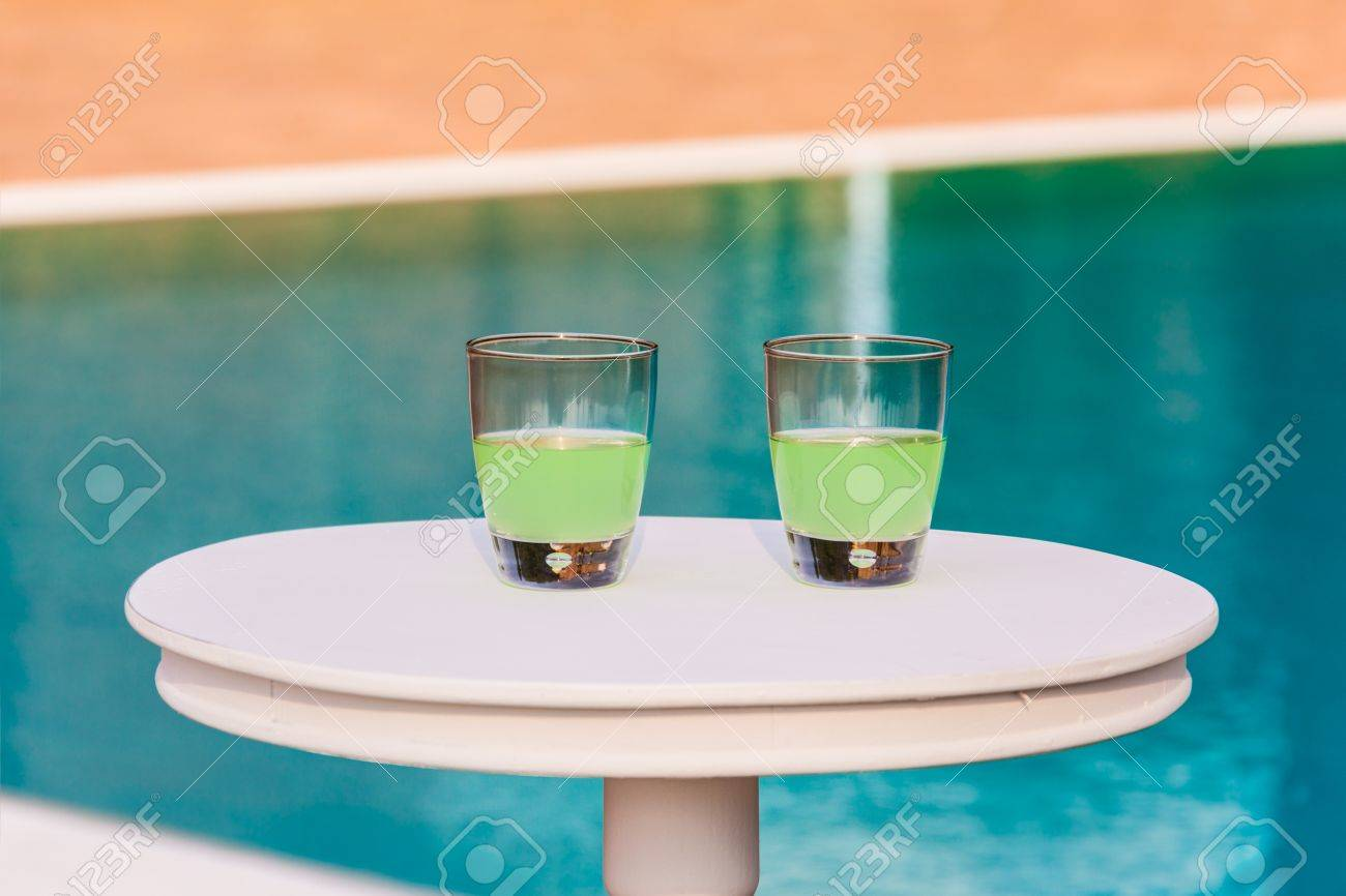 Two Drinks On A White Table With A Swimming Pool As Background Stock Photo    20435392