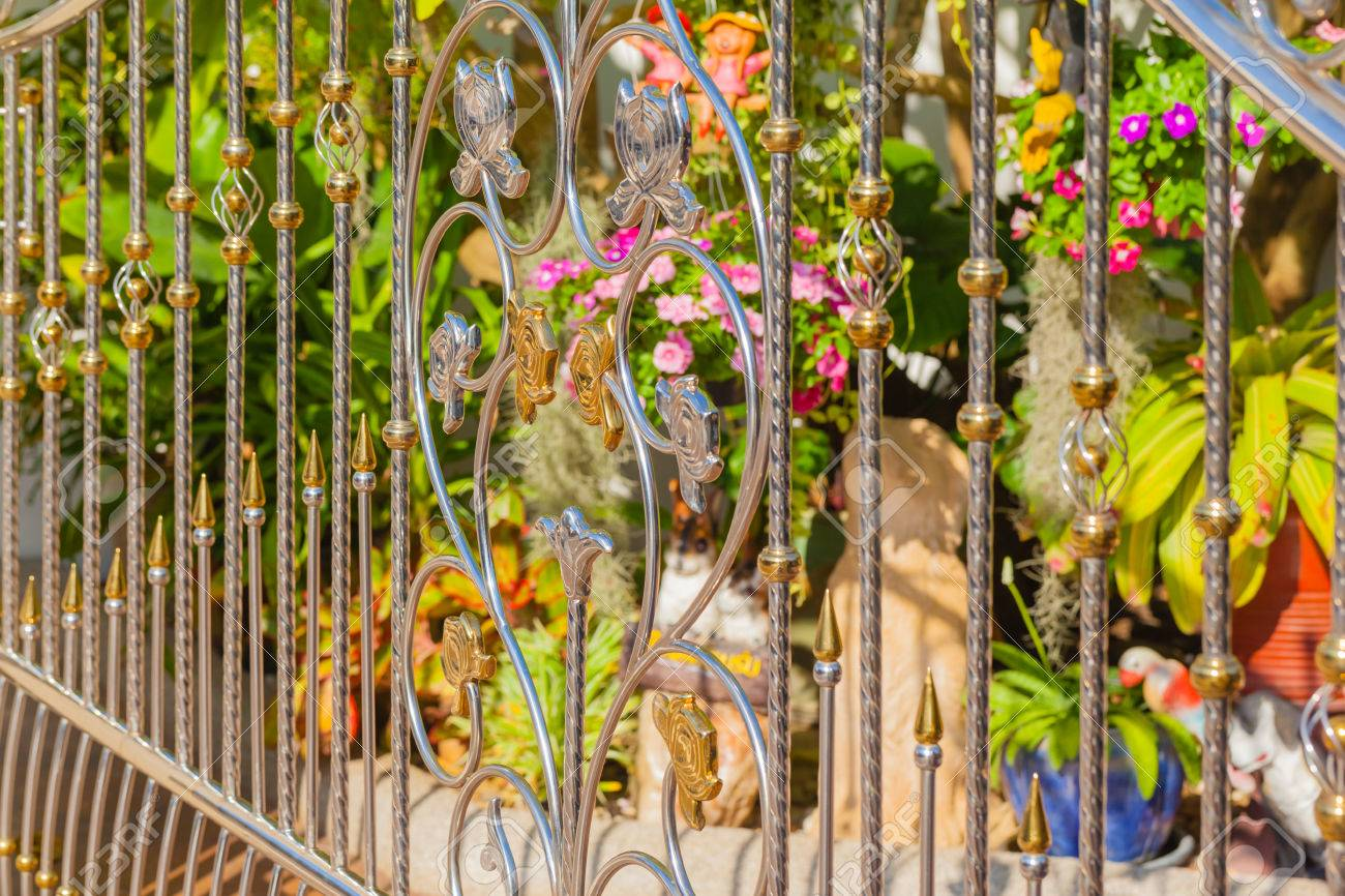 A Luxurious Chrome And Golden Gate With A Vibrant Garden In The ...