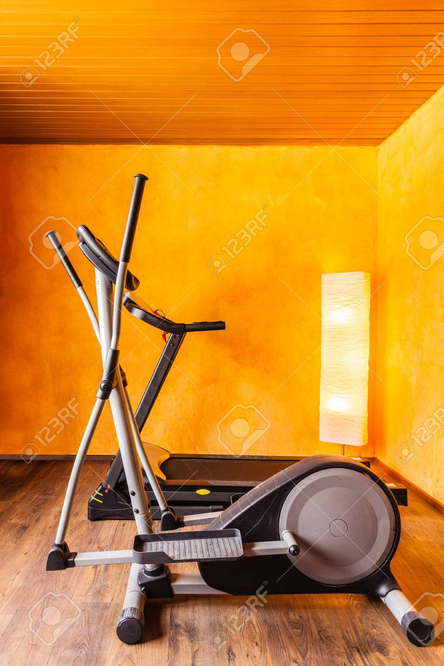 A small comfy home gym with a tread mill and an ellyptical machine