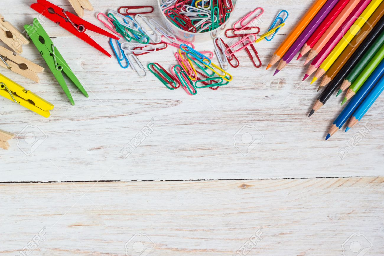 Desk of an artist, colorful pencils and paperclips on the white wooden table background - 44250378