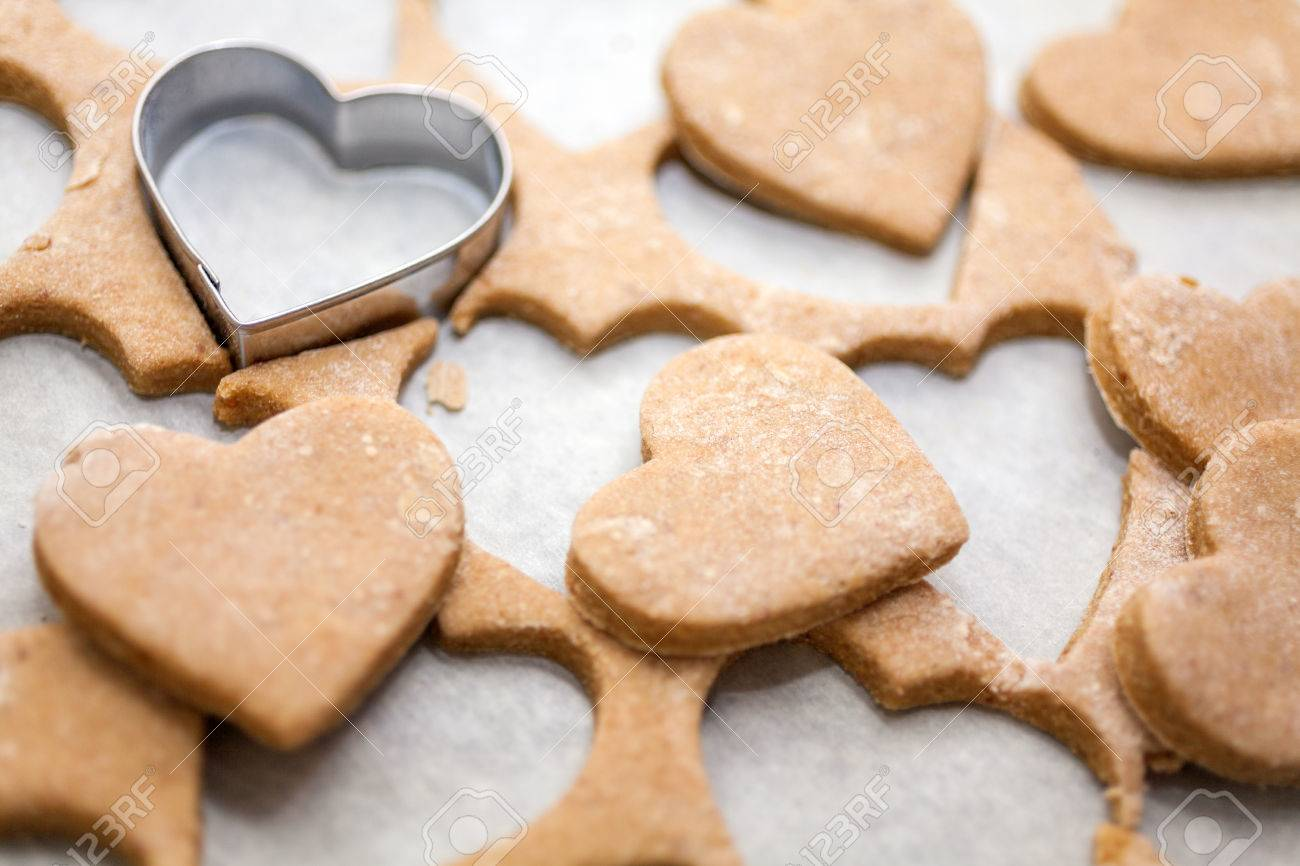 Heart Shaped Cookie Cutter On Raw Cookie Dough With A Few Cookies