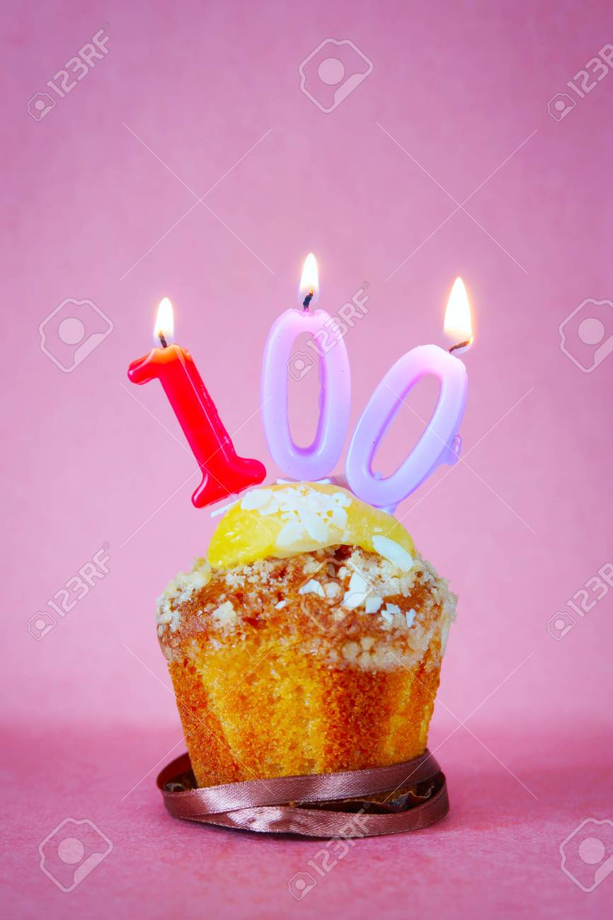 Muffin With Burning Birthday Candles As Number One Hundred On Pink Background Stock Photo