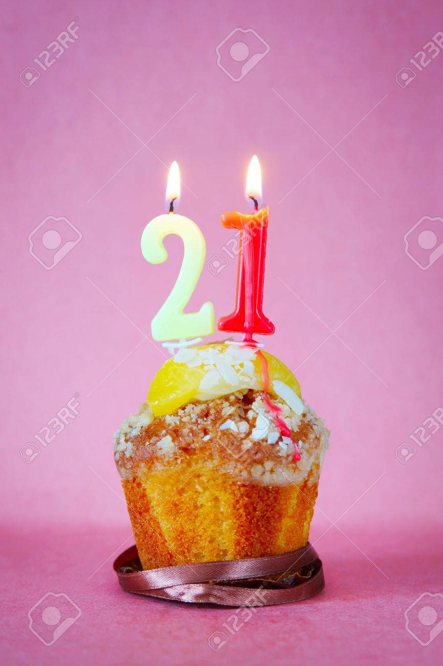 Muffin With Burning Birthday Candles As Number Twenty One On Pink Background Stock Photo
