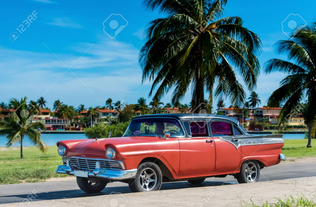 American Red Classic Car Parked Under Blue Sky Near The Beach In Havana Cuba