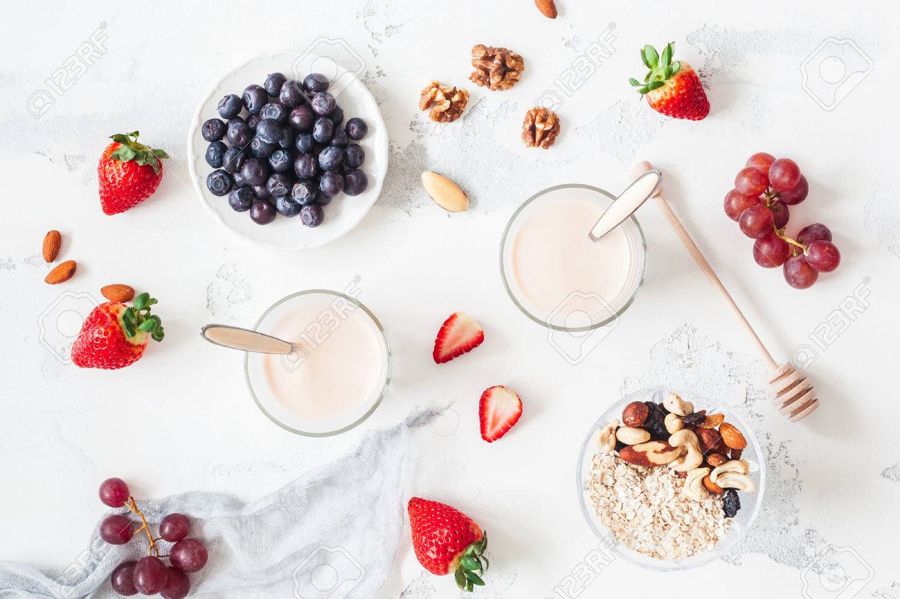 Breakfast with muesli, yogurt, strawberry, blueberry, nuts on white background. Healthy food concept. Flat lay, top view - 81119717