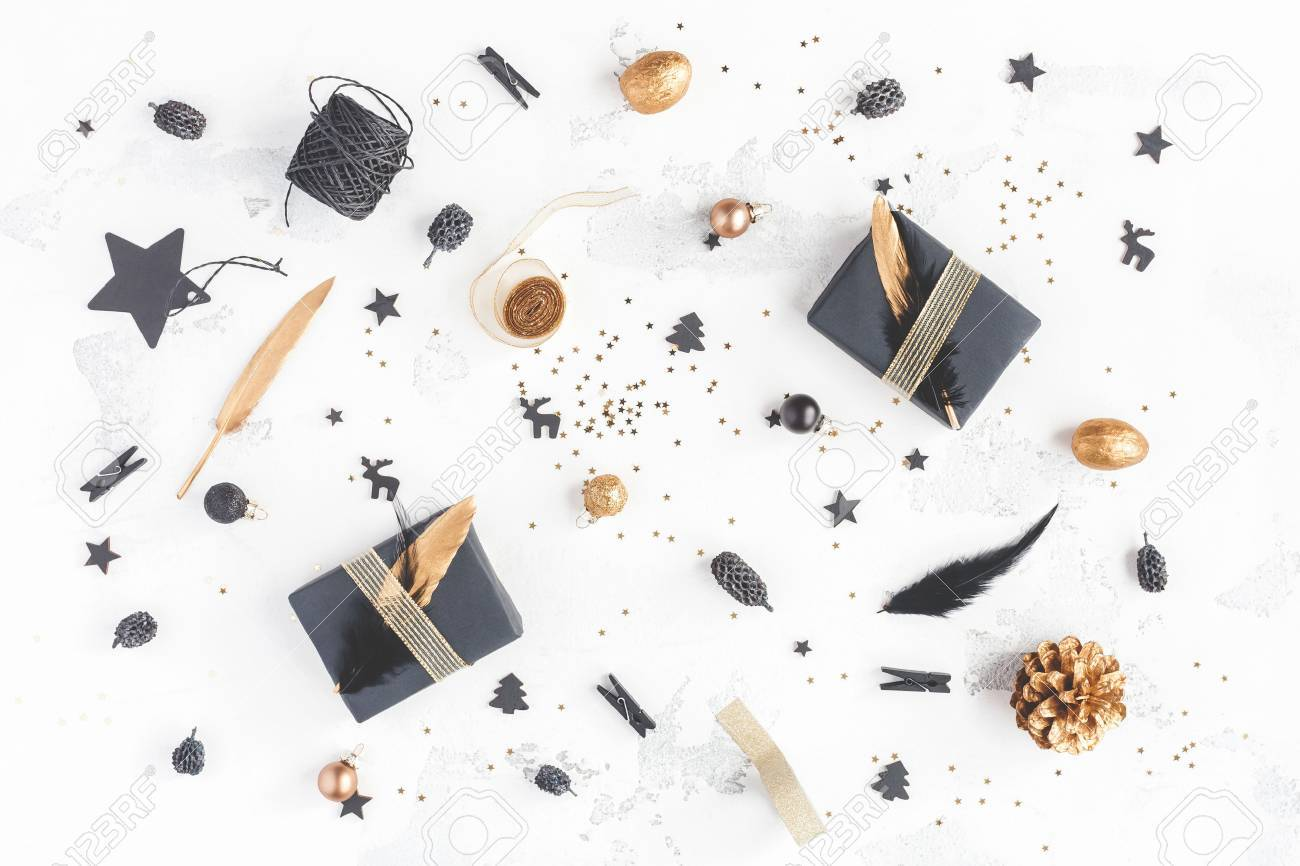 Christmas composition. Christmas gifts, pine cones, black and golden decorations on white background. Flat lay, top view - 87071270