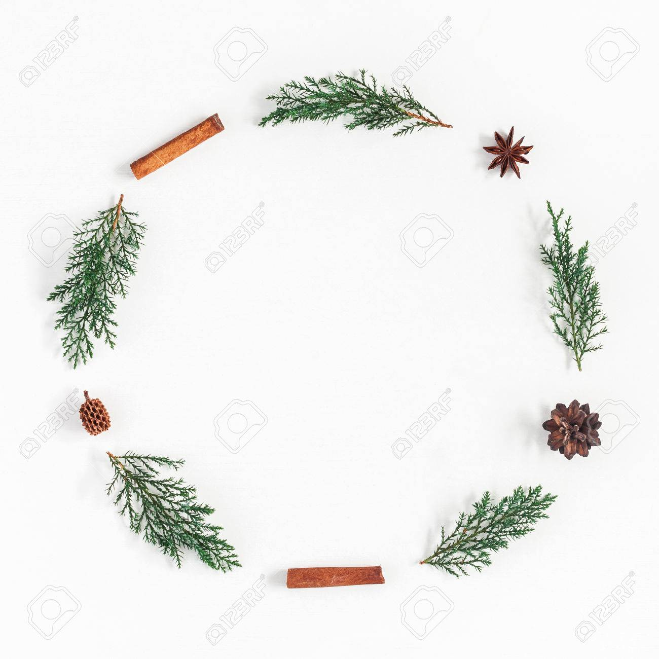 Christmas composition. Christmas wreath made of pine branches, cinnamon stick, anise stars on white background. Flat lay, top view, copy space, square - 87903435