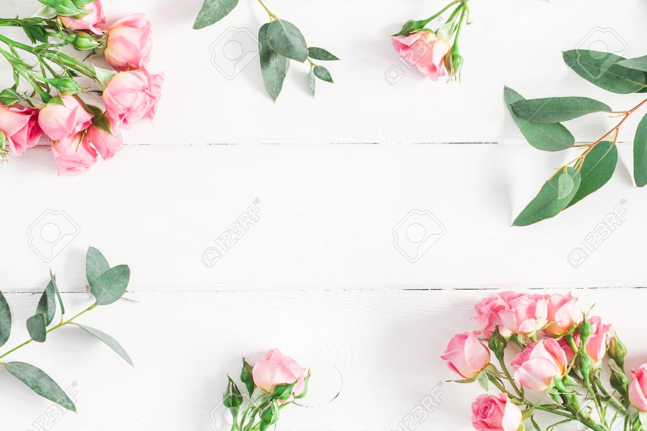 Flowers composition. Frame made of eucalyptus branches and pink rose flowers on white wooden background. Flat lay, top view, copy space - 93854917
