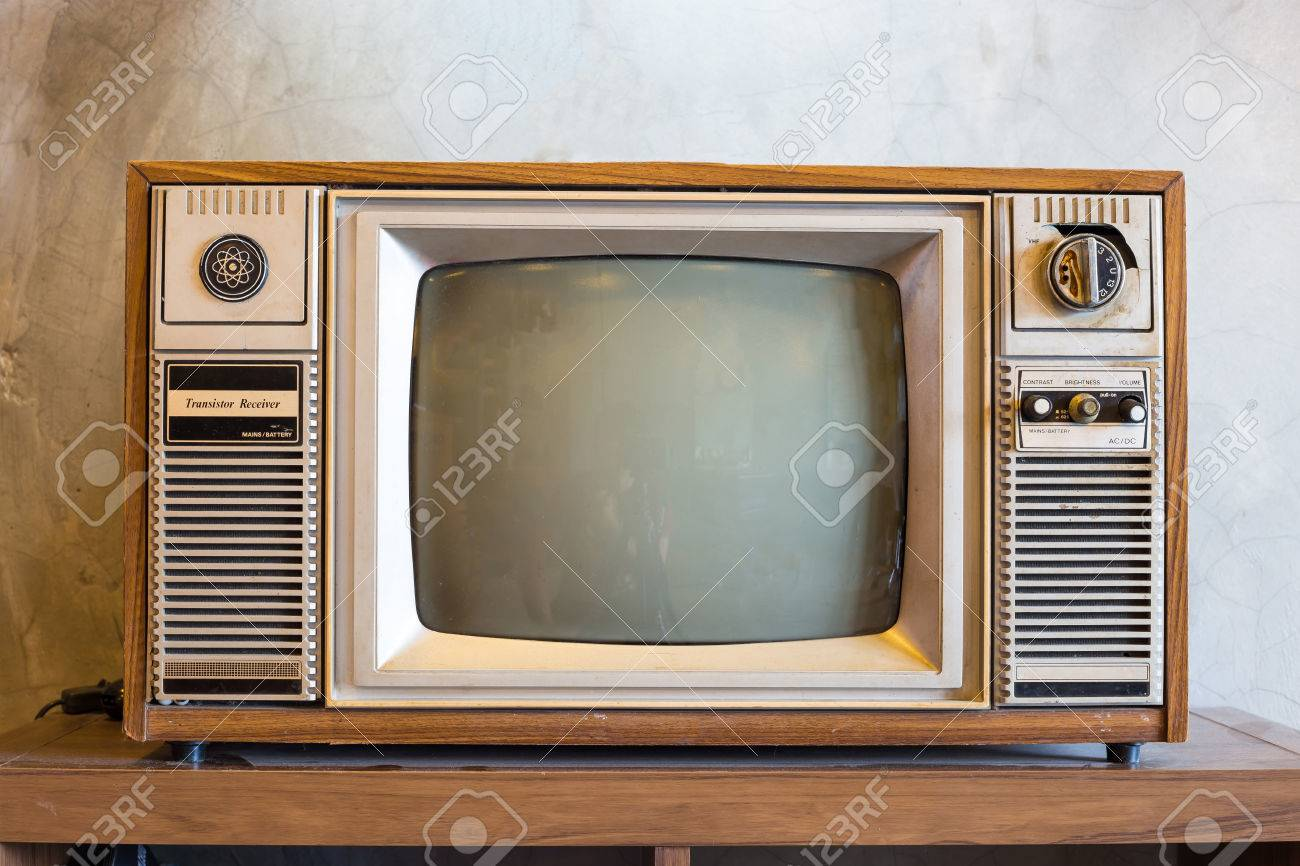 retro tv with wooden case in room with vintage wallpaper on wood table - 42038026