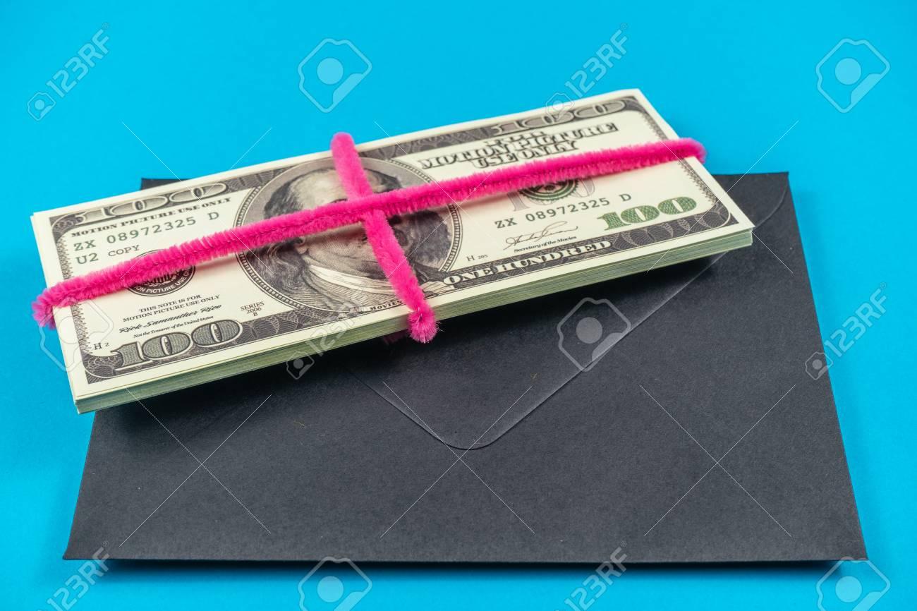 Prop Money Dollars and black envelope Light blue background