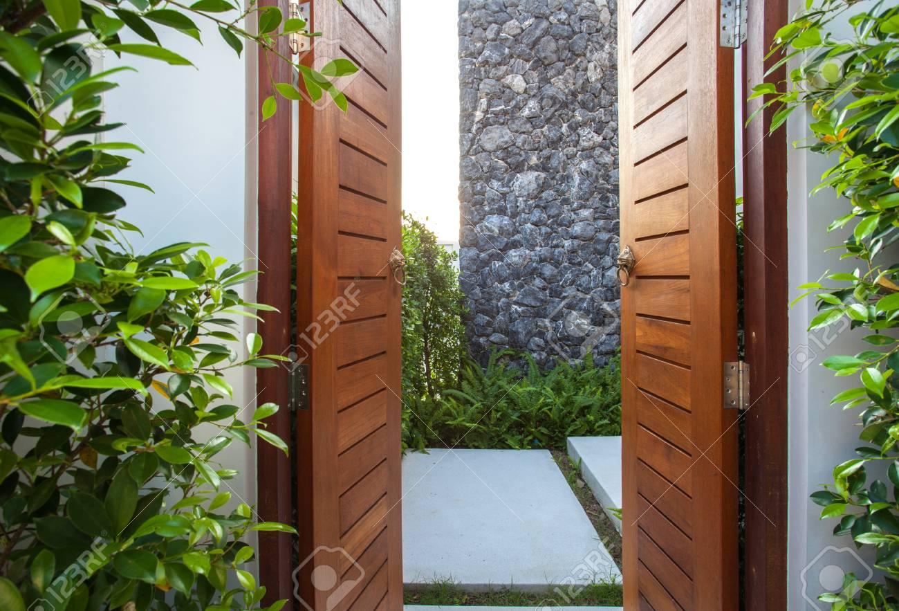 Diseno Interior Y Exterior De La Entrada Principal Que Cuenta Con Puerta De Madera Camino De Piedra Blanca Y Jardin
