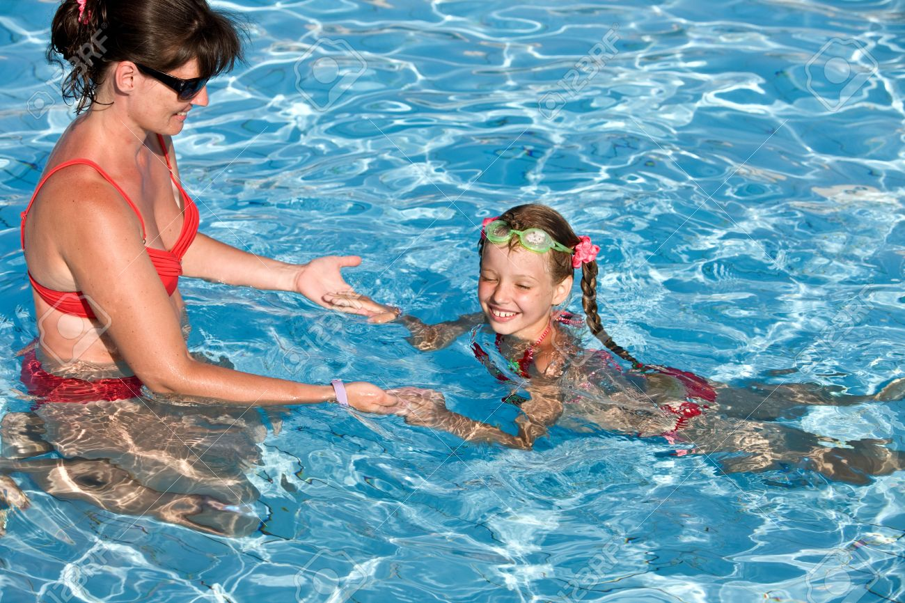 Instructor girl learn child swim in swimming pool. Stock Photo - 5775353