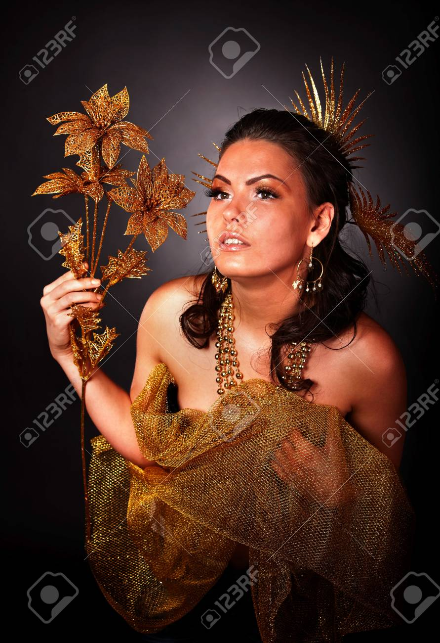 Beautiful young woman with gold flower on grey background. Stock Photo - 6283920