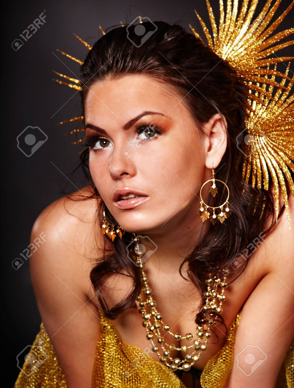 Beautiful young woman with gold flower on grey background. Stock Photo - 6283470