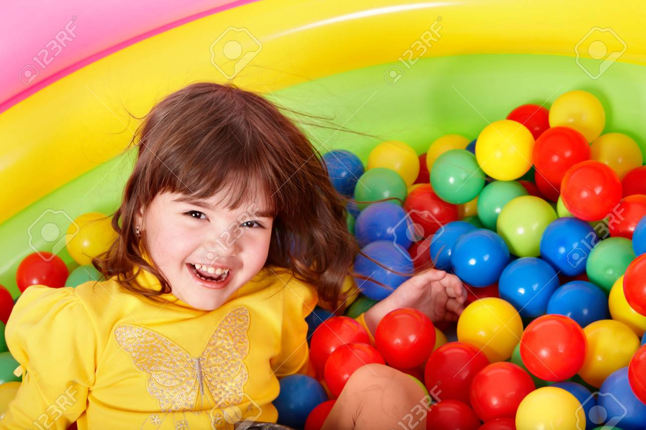 Happy little girl in group colourful ball. Stock Photo - 7779426