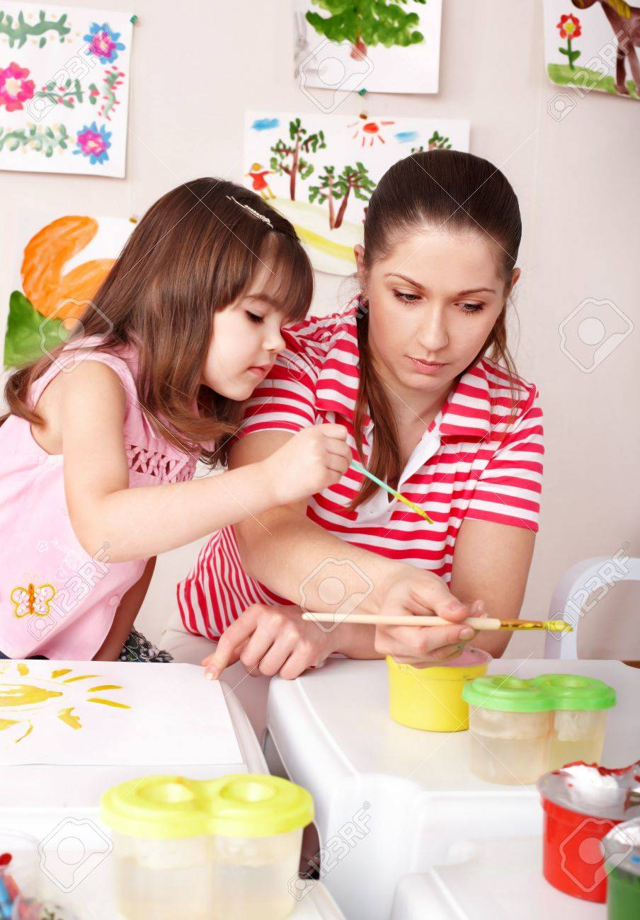 Little girl painting  with teacher in preschool. Stock Photo - 7779155