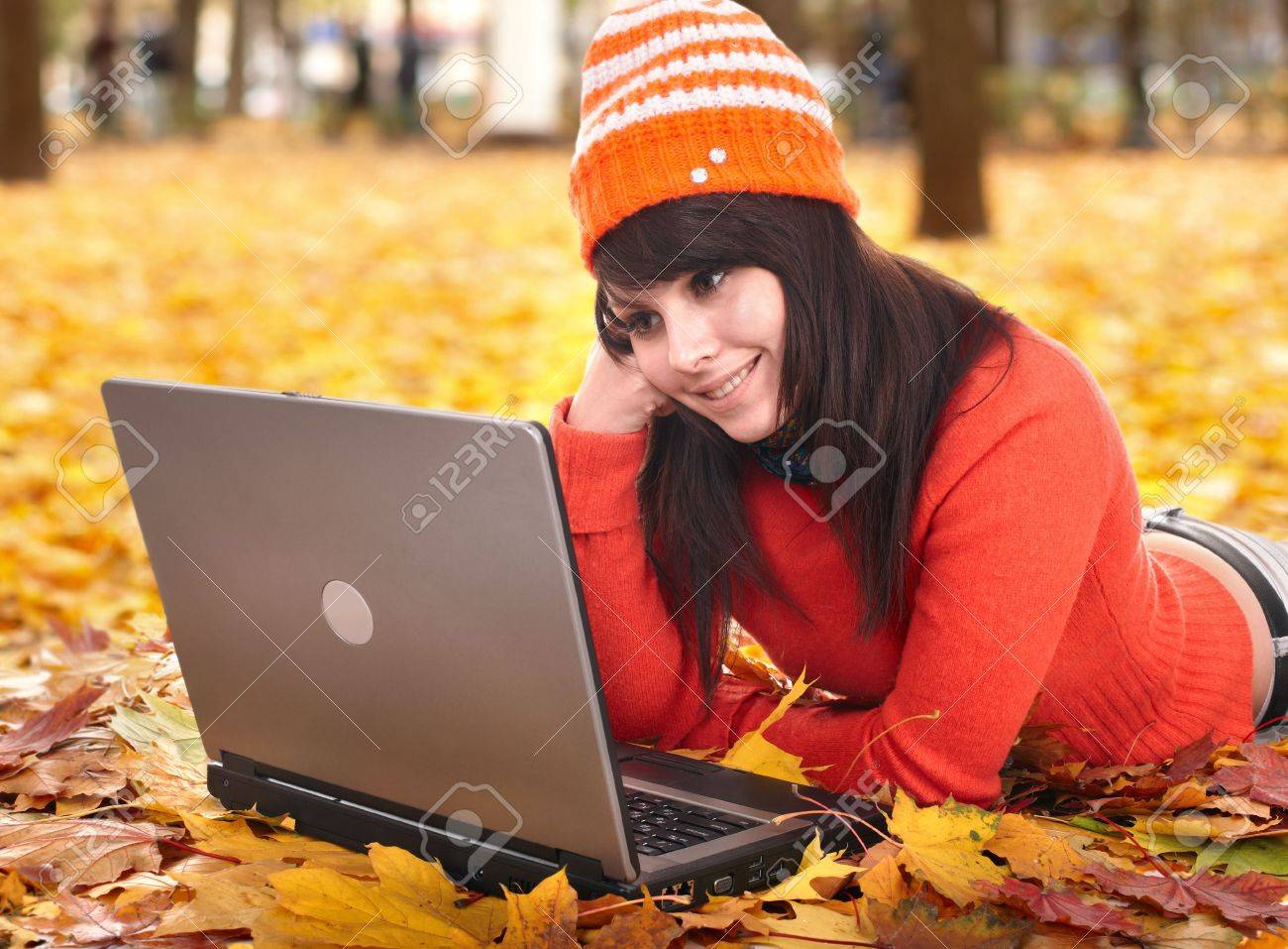 Young woman in autumn orange leaves with laptop. Fall sale. Outdoor. Stock Photo - 7779915