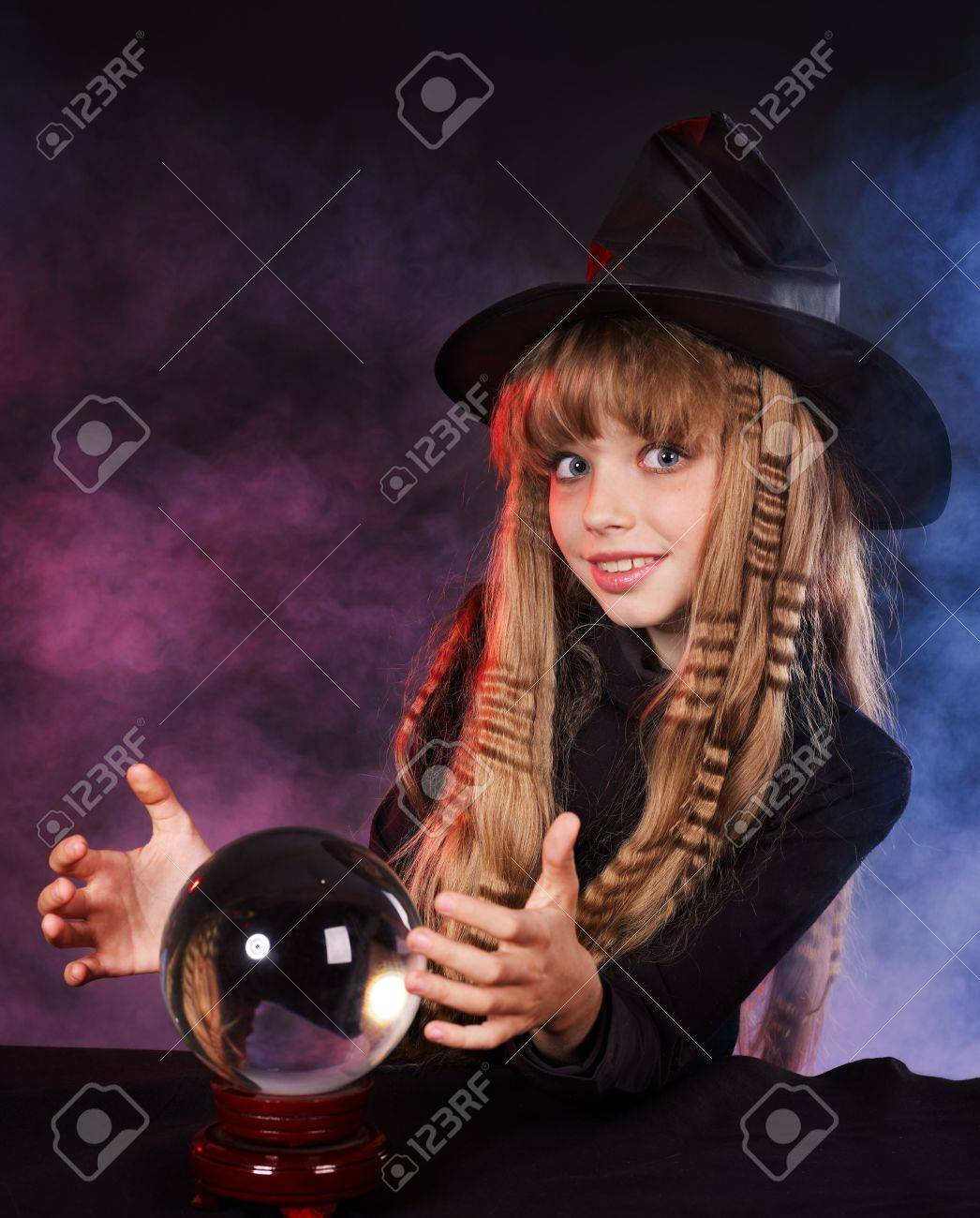 Little girl witch holding crystal ball. Stock Photo - 8116507
