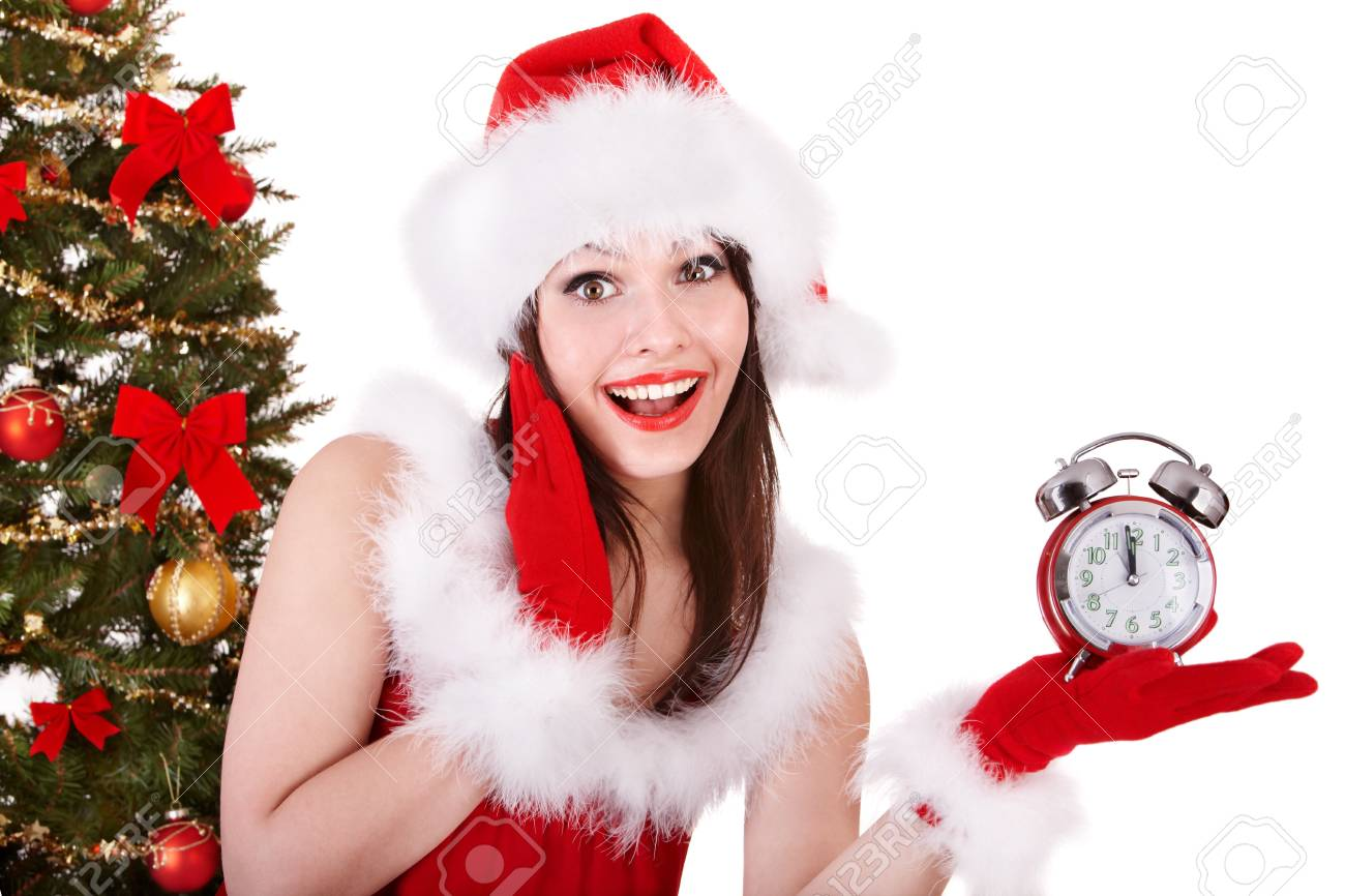 Girl in santa hat point on alarm clock by christmas tree.  Isolated. Stock Photo - 8405087
