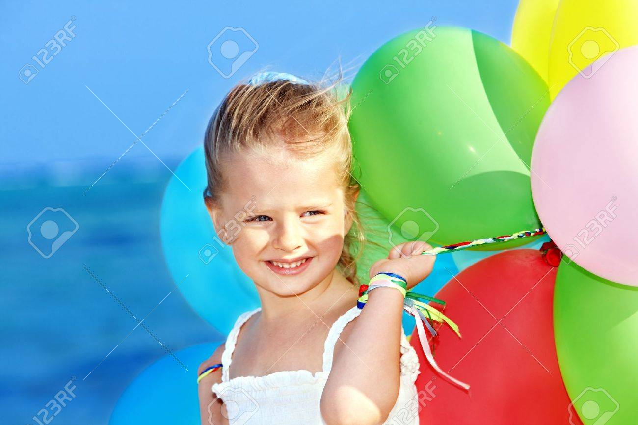 little girl playing with balloons at the beach. Stock Photo - 8942362