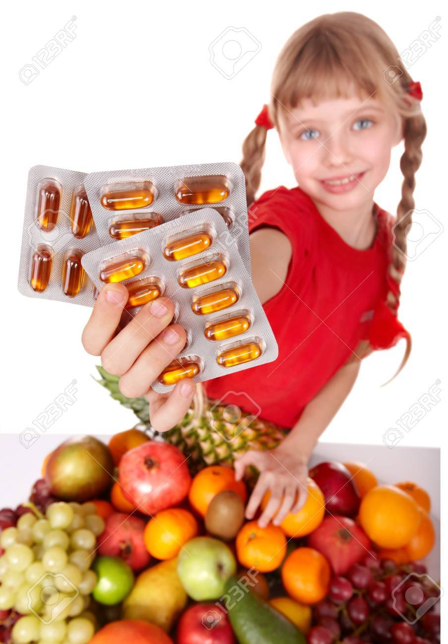 Child with fruit and vitamin pill. Isolated. Stock Photo - 9093872