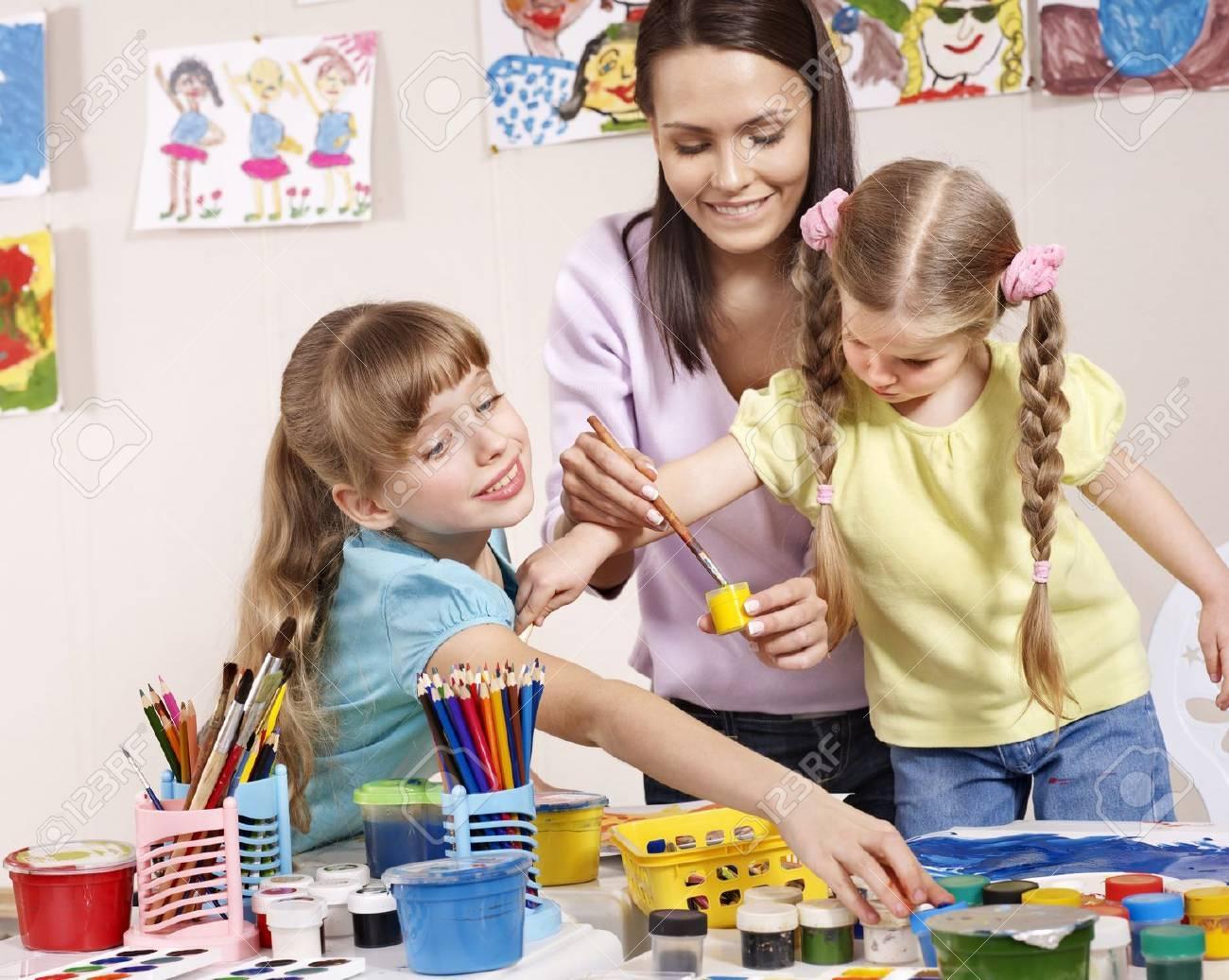 Child painting in preschool. Teacher help by little girl. - 9385720