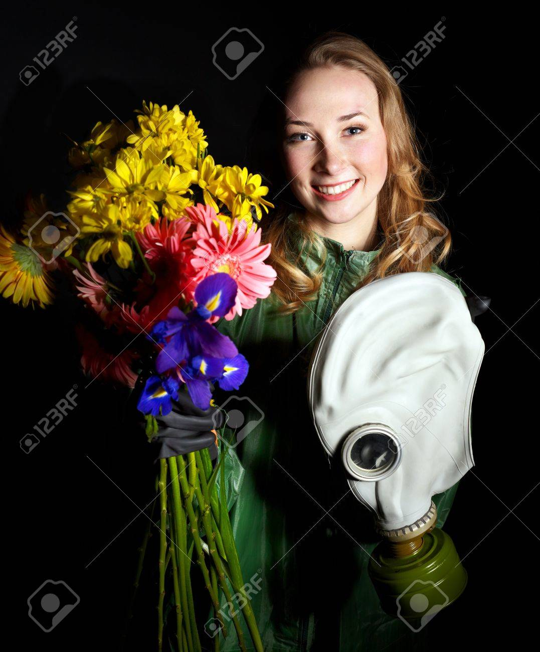 Young woman holding flowers and gas mask . Stock Photo - 9526568