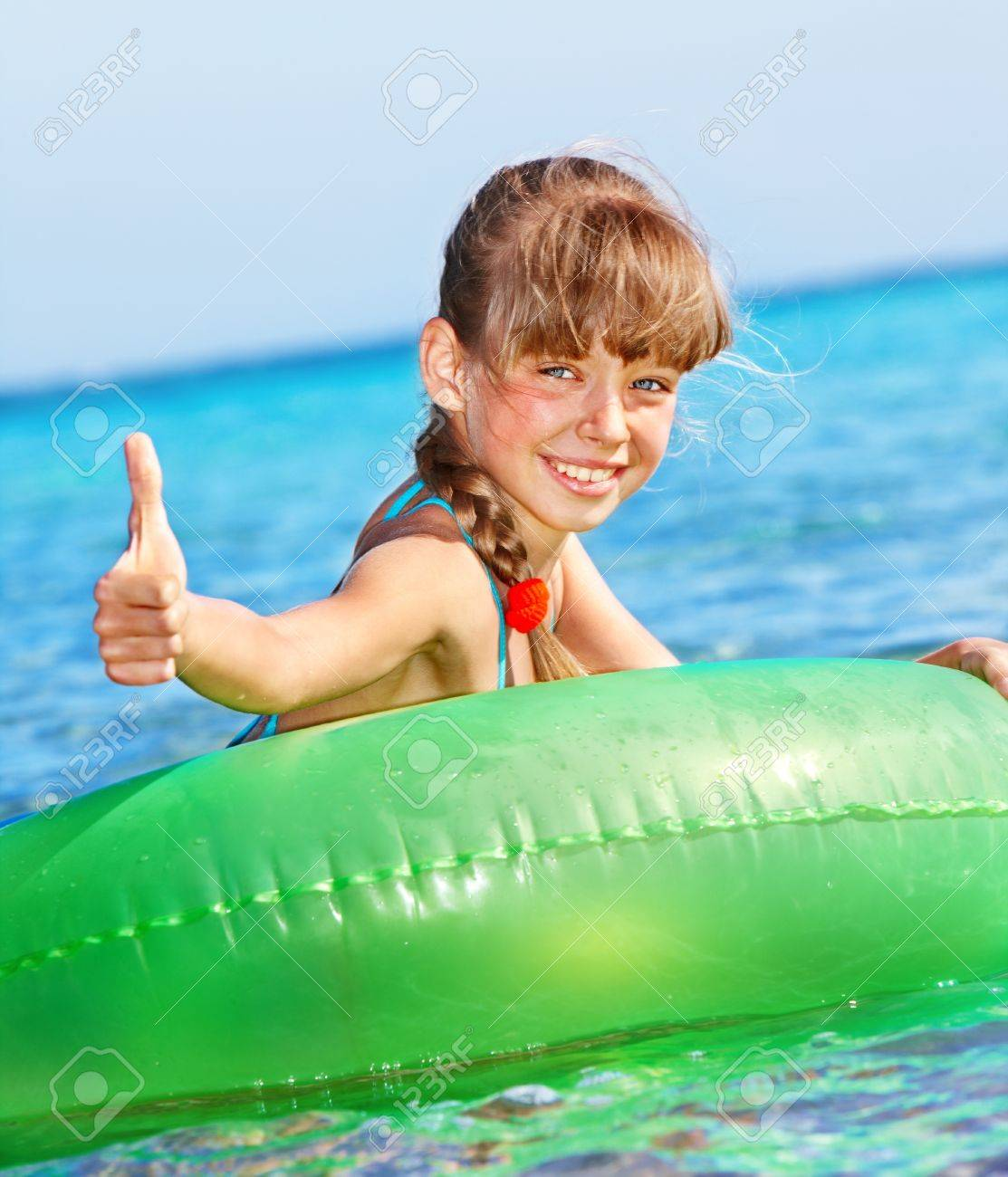 Children sitting on inflatable ring in swimming pool. Stock Photo - 9780990