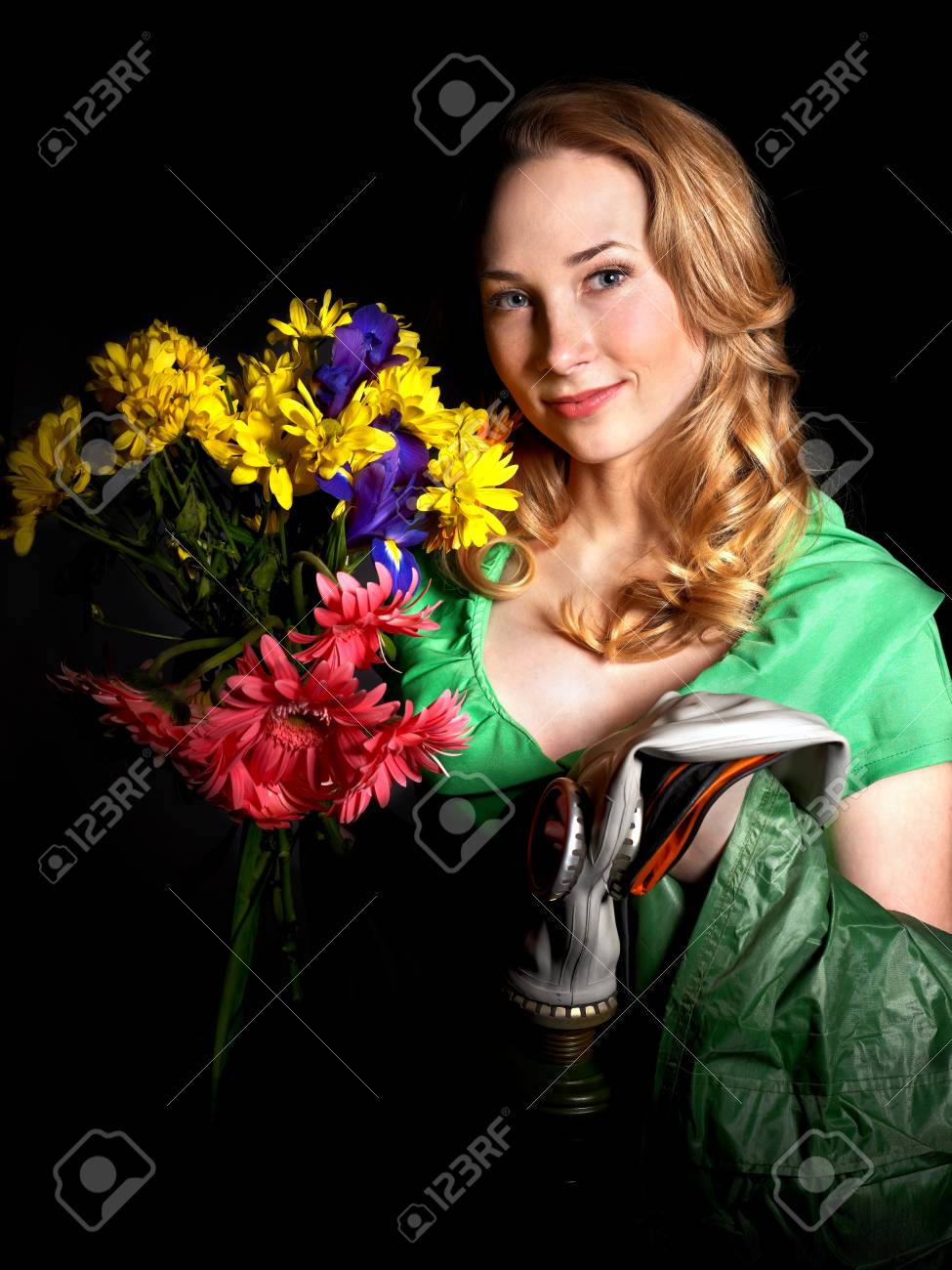 Young woman holding flowers and gas mask . Stock Photo - 9899455