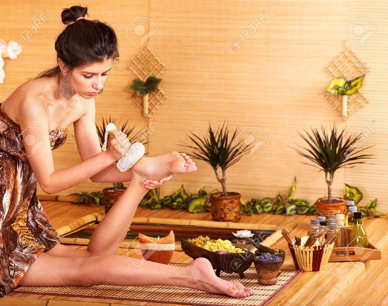 Young woman getting foot massage in bamboo spa. Stock Photo - 10778746