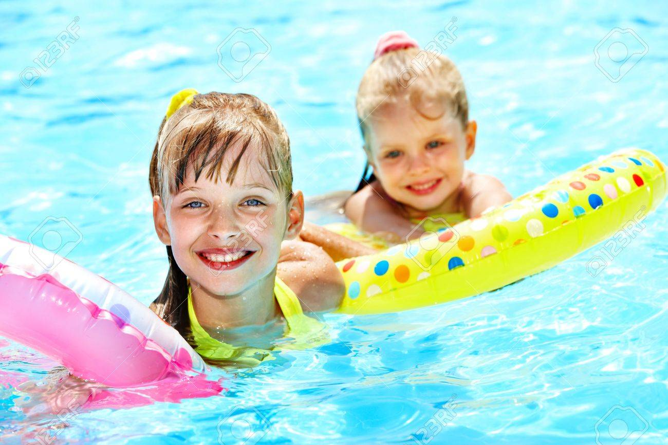 Children sitting on inflatable ring in swimming pool. Stock Photo - 12340822