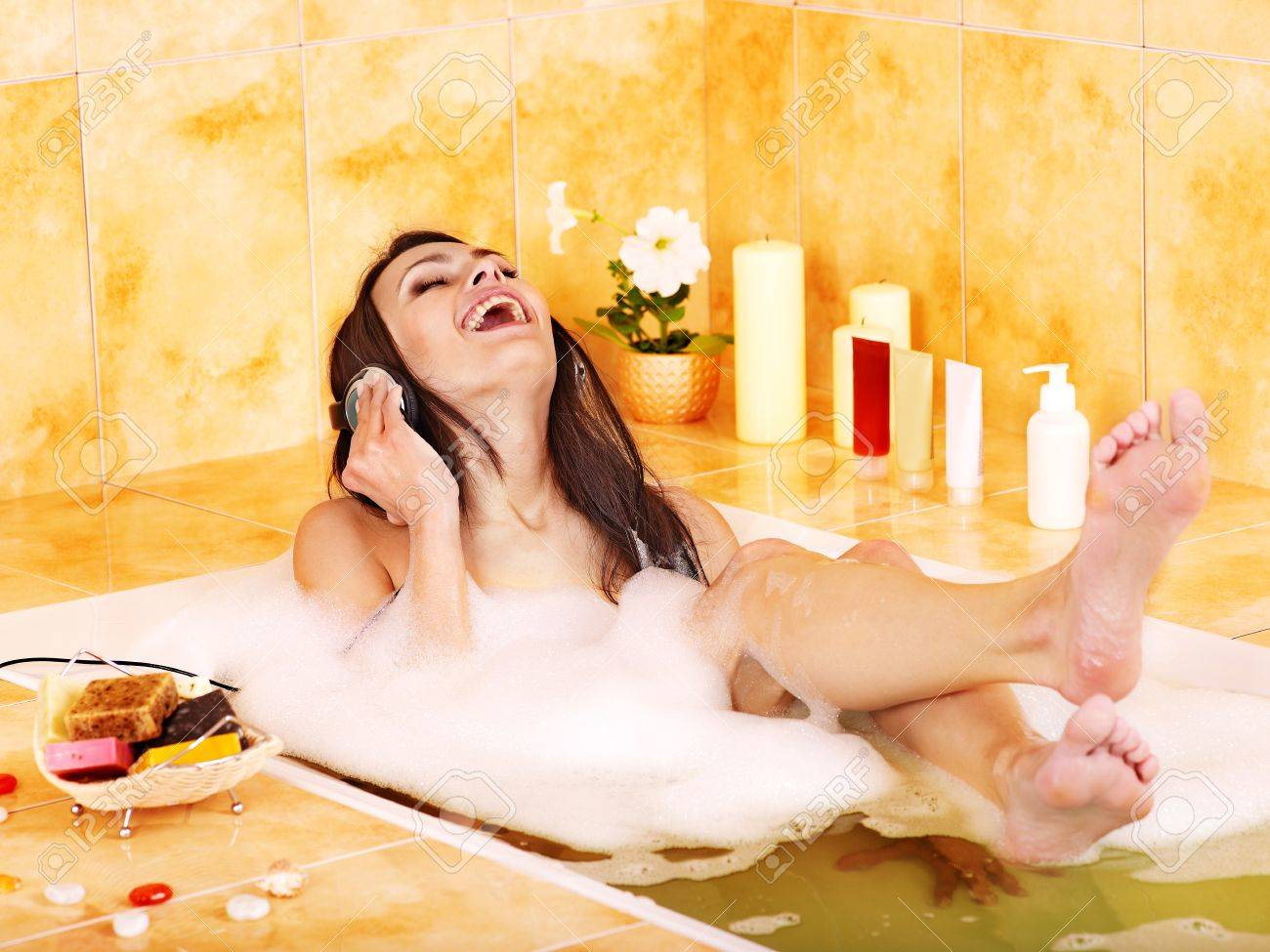 Woman listening to music in bubble  bath. Stock Photo - 12340851