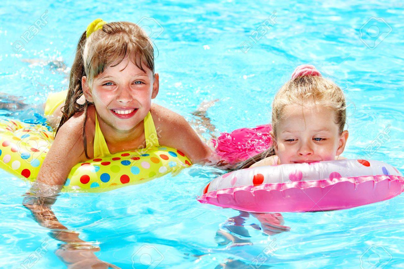 Children sitting on inflatable ring in swimming pool. Stock Photo - 12341081