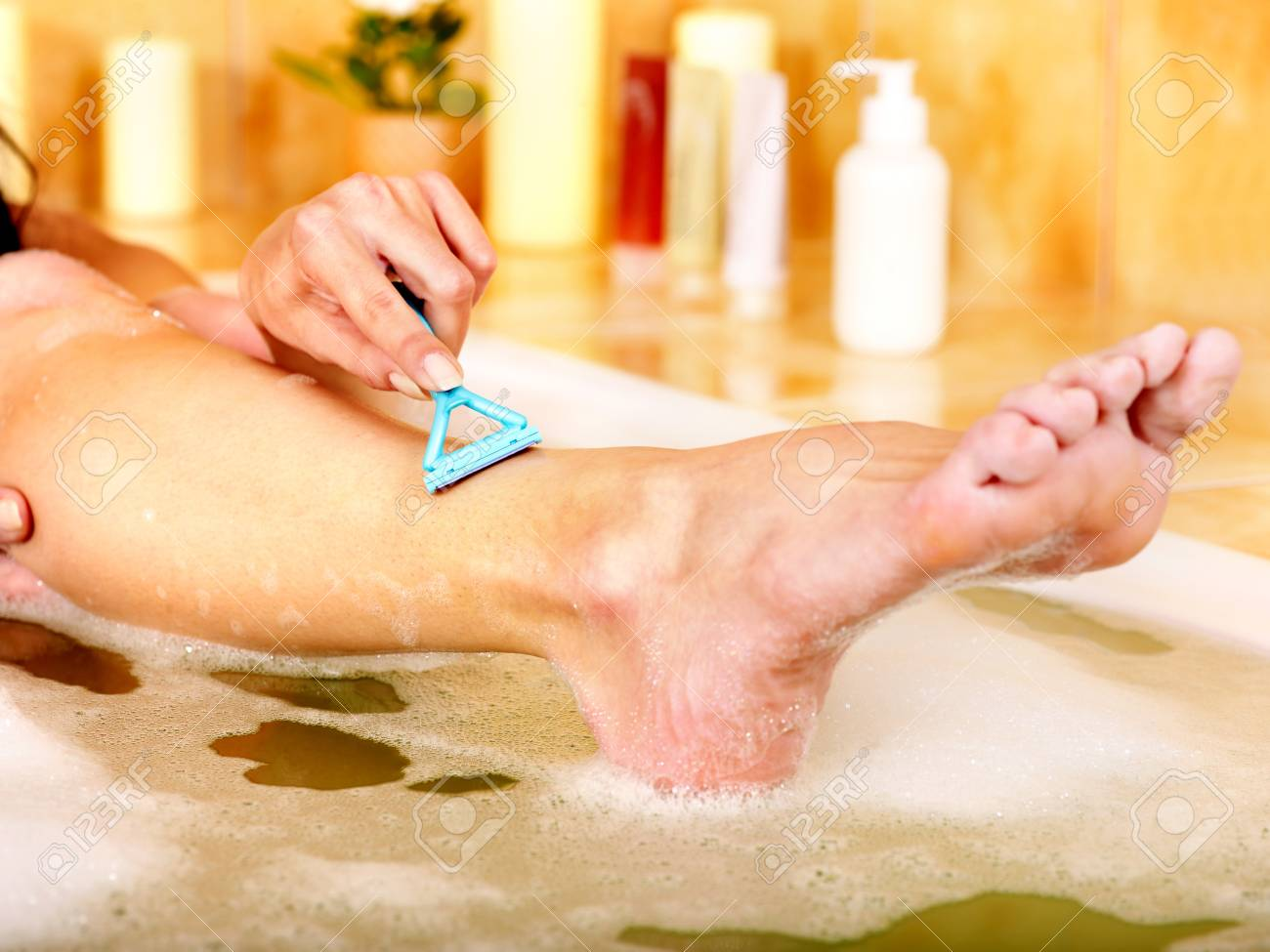 Young woman shaving her legs in  bath. Stock Photo - 12341077