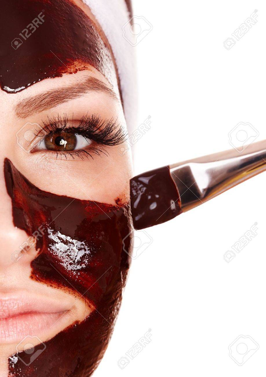 Girl having chocolate facial mask apply by beautician. Stock Photo - 13258952
