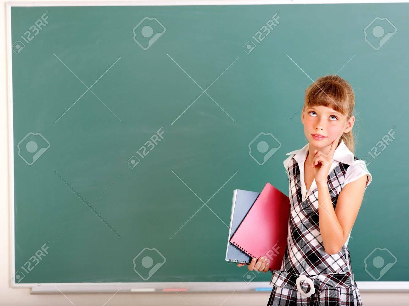 Happy schoolchild in classroom near blackboard. Stock Photo - 13258615