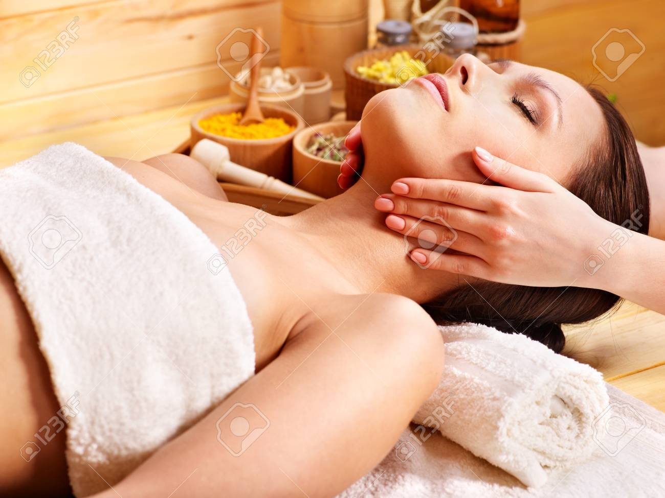 Woman getting facial  massage in wooden spa. Stock Photo - 13308320