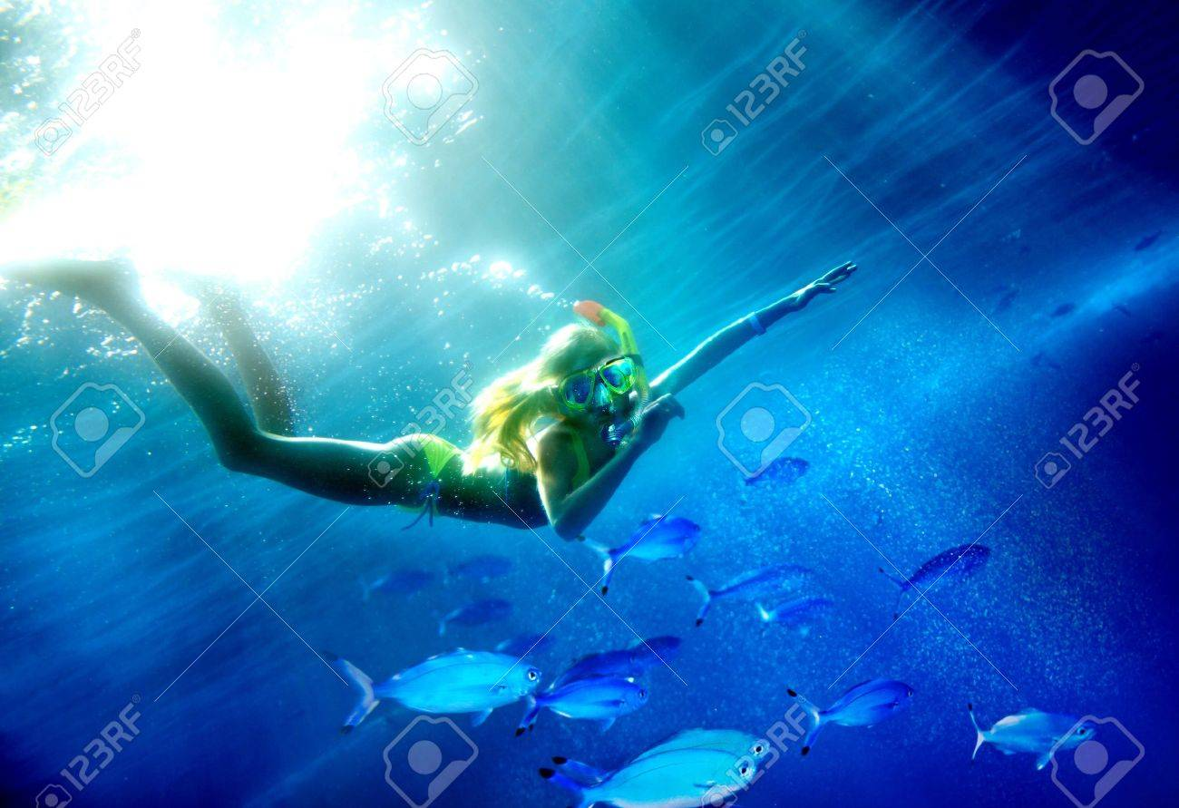 Child scuba diver with group coral fish in  blue water. Stock Photo - 14523813
