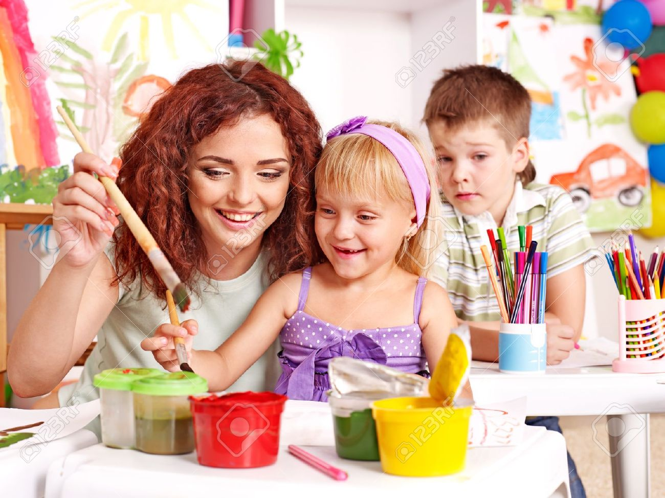 Children with teacher painting at easel in school. Stock Photo - 14743042