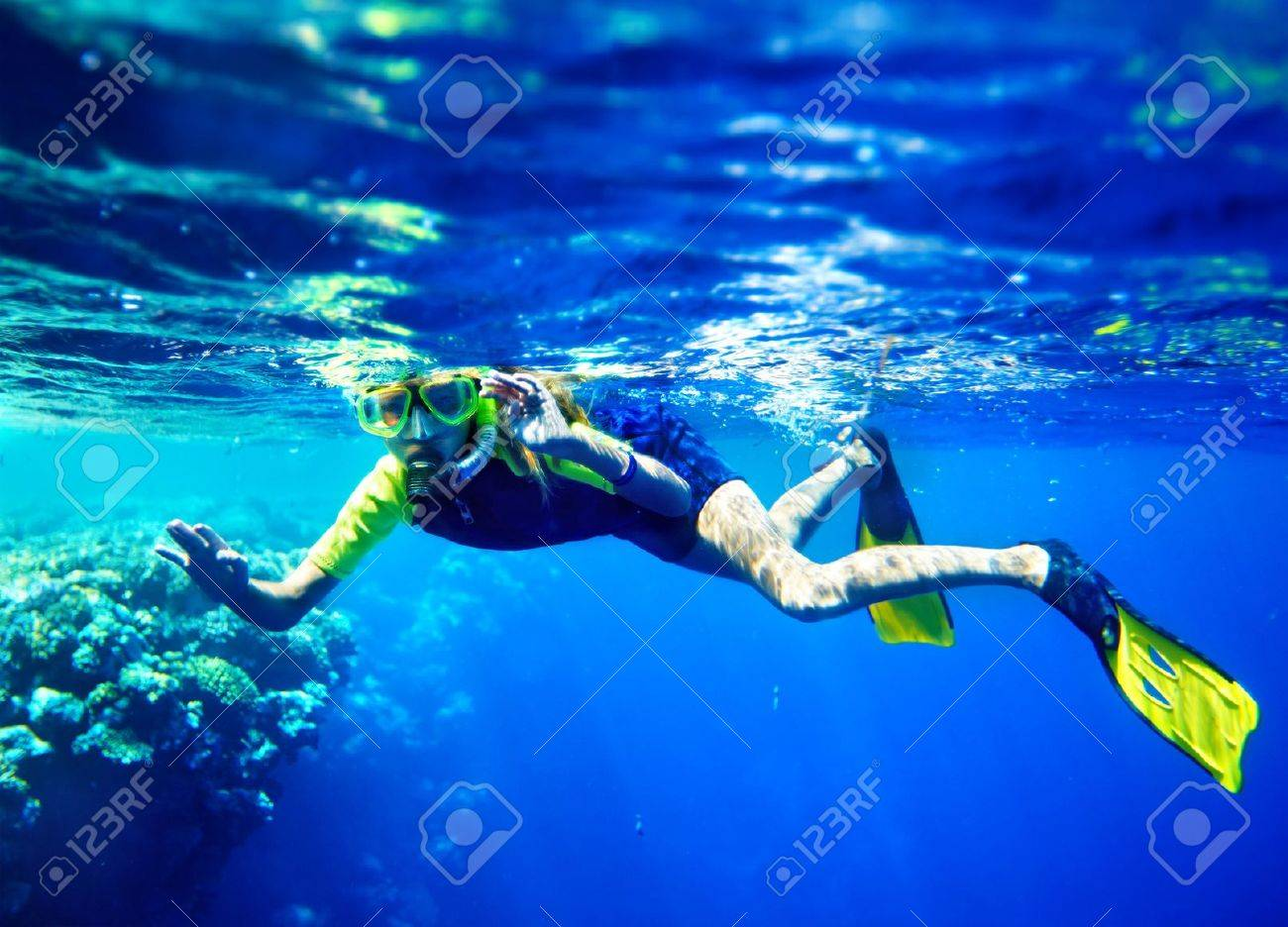Child scuba diver with group coral fish in  blue water. Stock Photo - 15231411