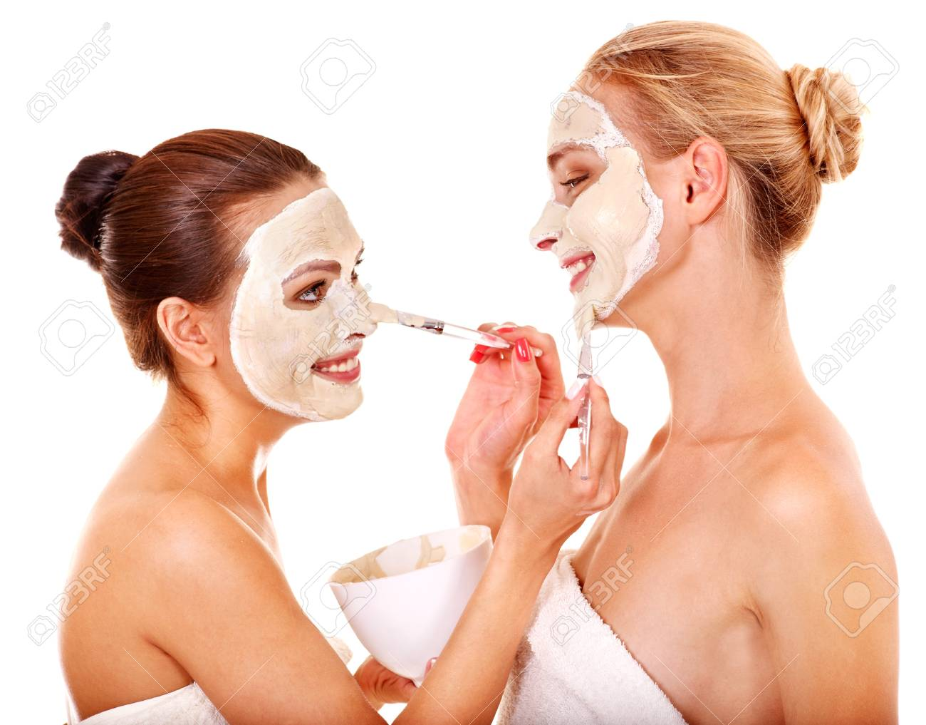 Young woman getting facial mask and gossip . Isolated. Stock Photo - 16609837