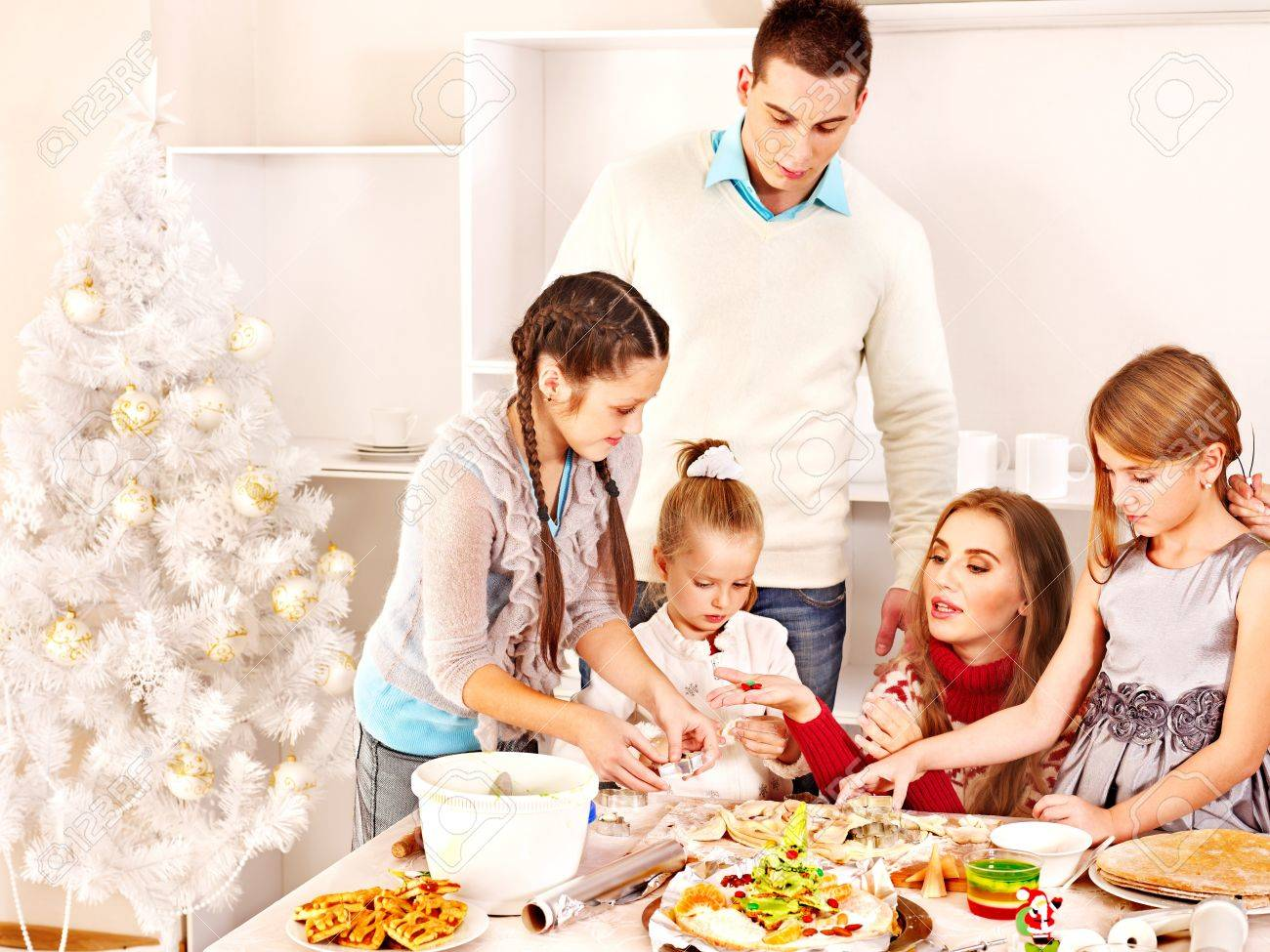 Happy family in kitchen - Happy Family With Children Rolling Dough In Christmas Kitchen Stock Photo 16612998