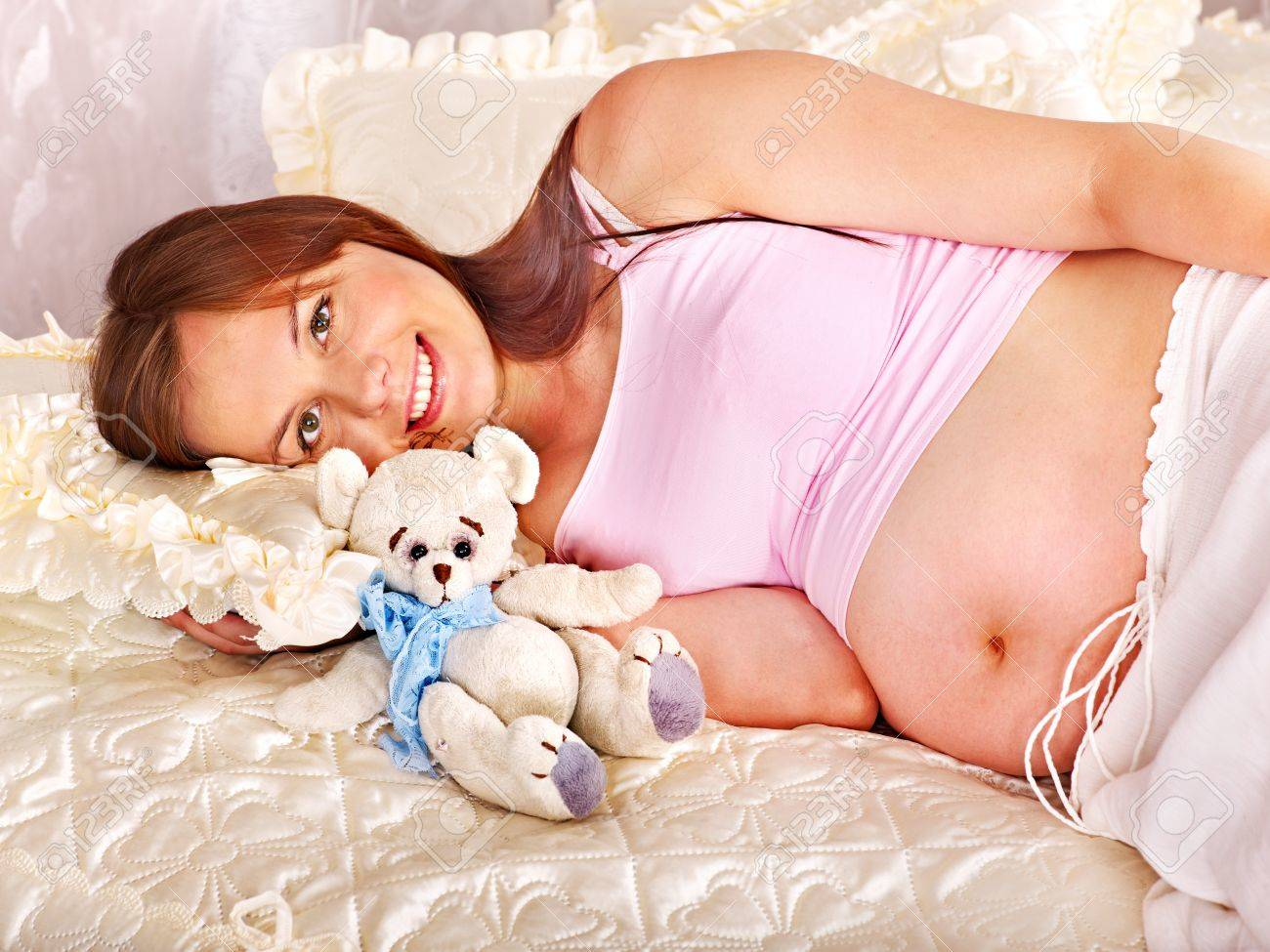 Pregnant woman holding teddy bear at bedroom. Stock Photo - 17405311