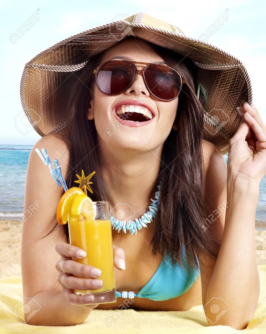 Young woman in bikini on beach drinking cocktail. Stock Photo - 17753912
